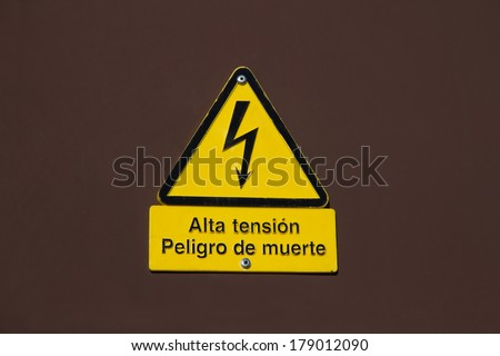 Signal of danger of death by high voltage in Spanish in metallic brown wall