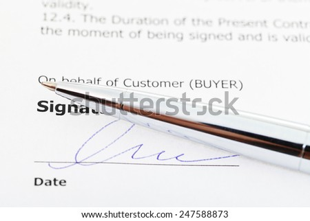 signature of sales agreement and silver pen close up