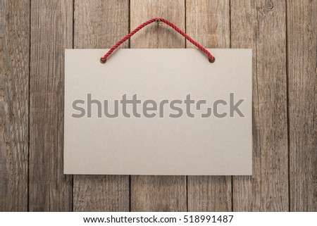 Signboard with rope on wooden background