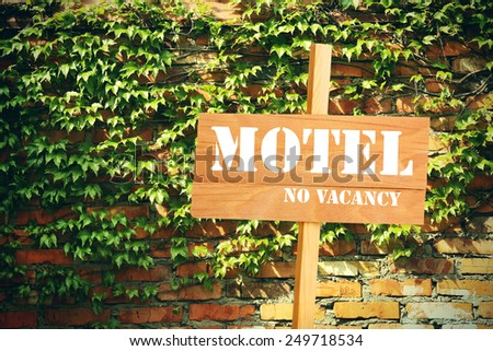 Signboard with text Motel, No Vacancy near hotel on brick wall background - stock photo