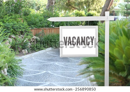 Signboard with text Vacancy near hotel - stock photo