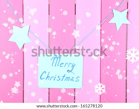 Signboard with words Merry Christmas on pink wooden table background close-up - stock photo