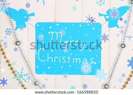 Signboard with words Merry Christmas on wooden table background close-up - stock photo