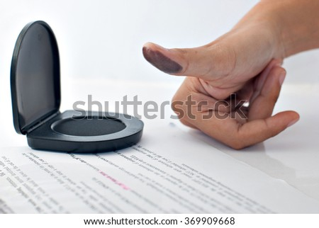 Signing a contract with a thumb print: Image contains thumb with ink stain with paper and ink stamp pad. - stock photo