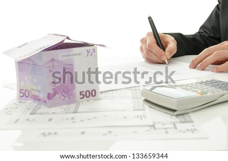 Signing contract of house sale with house made of 500 Euro money and  architectural building plan on a white table. - stock photo