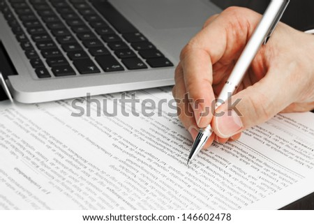 Signing Contract with Laptop and pen and hand - stock photo