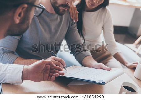 Signing documents. Close-up of confident young man signing some document while sitting together with his wife and another man pointing document  - stock photo