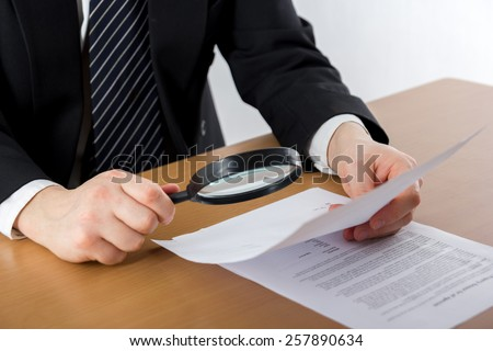 Signing papers. Lawyer, realtor, businessman sign documents, looking through the magnifying glass, search information.  - stock photo