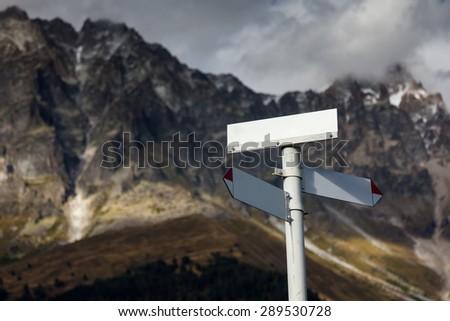 Signpost against big Caucasus mountains - stock photo