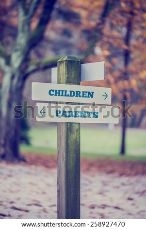 Signpost in a park or forested area with arrows pointing two opposite directions towards Children and Parents. Conceptual of a fun adventurous day with separate activities for the kids and adults.