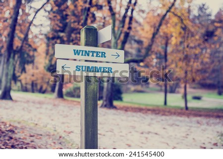 Signpost in a park or forested area with arrows pointing two opposite directions towards Winter and Summer. - stock photo