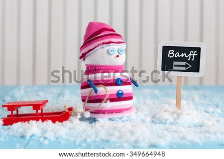 Signpost of the famous Banff National Park, Alberta, Canada and Snowman with red sled stand near direction sign. Postcard. - stock photo