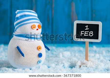 Signpost of the 1 February and Snowman  stand near direction sign. Happy winter postcard  - stock photo