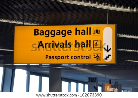 Signpost pointing towards baggage and arrivals hall and passport control at Amsterdam Schiphol airport - stock photo