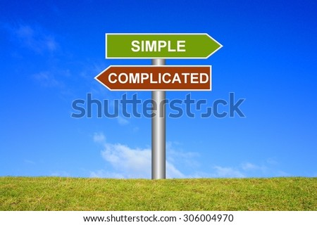 Signpost sign with blue sky and green grass showing simple or complicated - stock photo