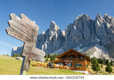 Signpost with alpine hut and Geisler mountains, Val di Funes, South Tyrol, Italy - stock photo
