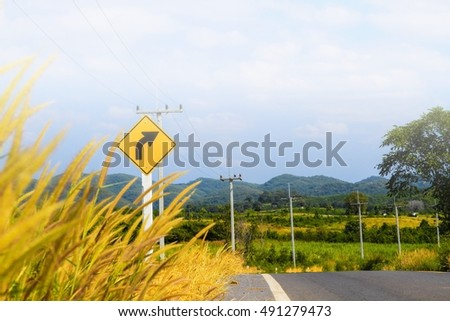 Signroad on highway with grass flowers