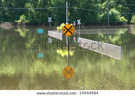 Signs and fences are submerged in flood waters.