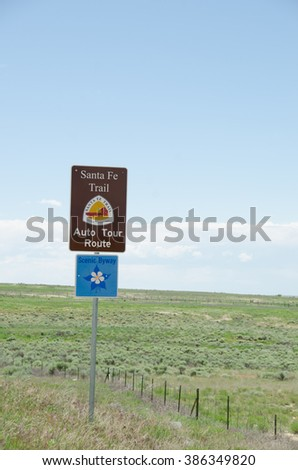 Signs for the Santa Fe Trail National Historic Trail Auto Tour Route with a covered wagon and team of oxen and a Colorado Scenic Byway with a Columbine - Colorado's State Flower