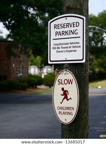 Signs in a parking lot, warning of authorized parking only and children at play. - stock photo