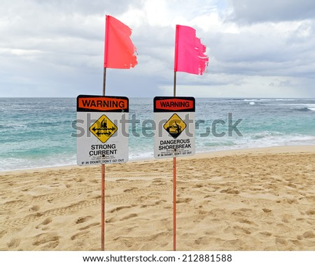 Signs on Sunset Beach warn off strong current and a dangerous shorebreak. - stock photo
