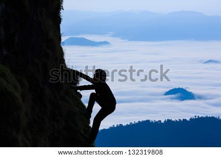Sihouette businessman climbs a mountain - stock photo