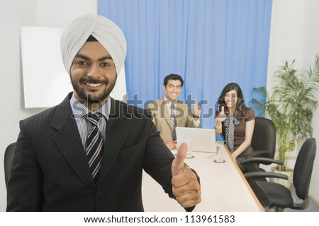 Sikh business executives showing thumbs up and smiling