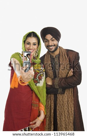 Sikh couple taking a picture of themselves with a mobile phone - stock photo