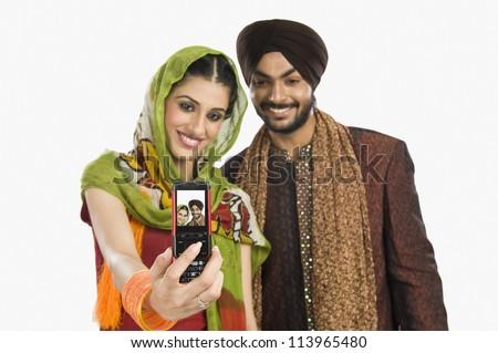 Sikh couple taking self-portrait - stock photo