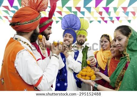 Sikh people eating laddoos - stock photo
