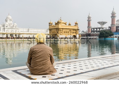 Sikh pilgrim at the Golden Temple in Amritsar, Punjab, India. The Golden Temple is the holiest pilgrimage site for the Sikhs. - stock photo