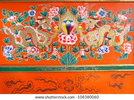 SIKKIM/ INDIA-JUNE 12: Pair of dragons, Chrysanthemum flowers, and conch shells; painting on wood inside worship room in a general person house on June 12, 2012 in Sikkim. - stock photo