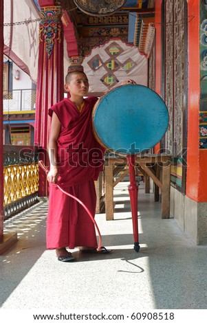SIKKIM, INDIA - MAY 17:  monk with drum at Rumtek Monastery on May 17, 2010 in Sikkim, India, Rumtek is the biggest monastery of Kagyu sect of tibetan buddhism in Sikkim. - stock photo
