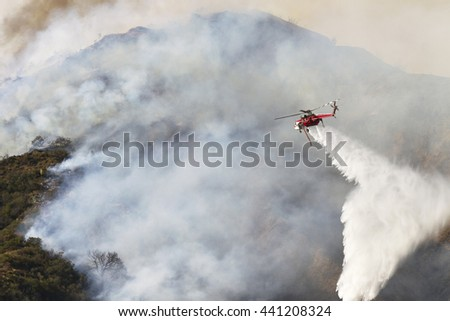 Sikorsky S-64 SkycraneType I Heavy lift Helicopter, drops water on a brush fire.