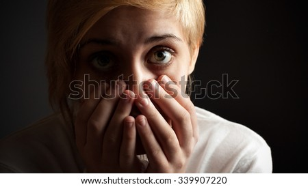 Silence or fear. Portrait of a girl in low key. Close up - stock photo