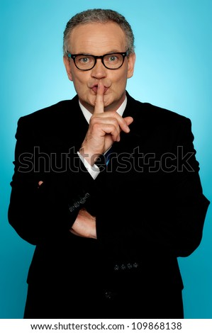 Silence please, businessman looking at you with finger on his lips - stock photo