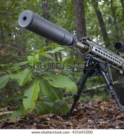 Silencer mounted on a semi automatic rifle in a forest - stock photo