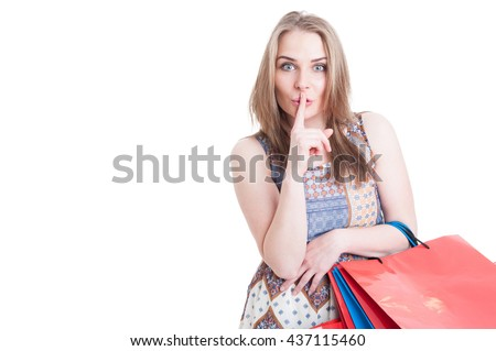 Silent concept with stylish beautiful woman doing shush gesture and holding shopping bags isolated on white - stock photo