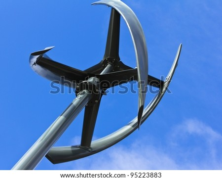Silent urban styled wind turbine, low angle view, blue sky. - stock photo