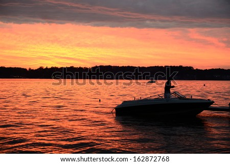 Silhoette of man fishing on boat in colorful evening sunset.