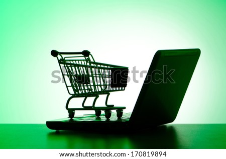 Silhoette of shopping cart and laptop - stock photo