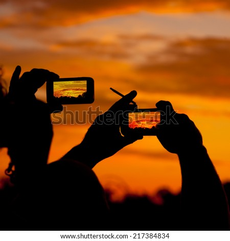 Silhoettes of people taking pictures of burning sunset sky horizon