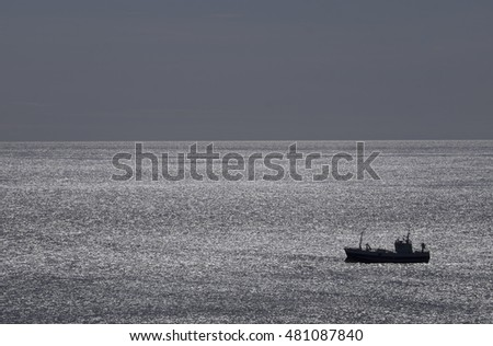 Silhouet of a fishing boat which floats on waving water in Iceland