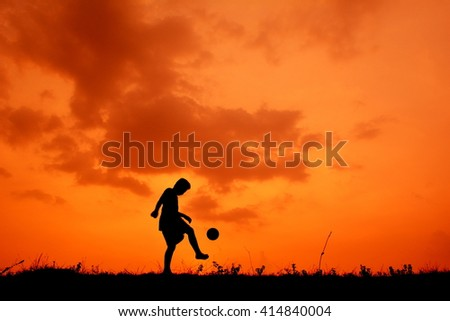 Silhouette a boy playing football in the sunset - stock photo