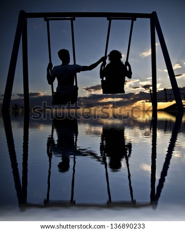 silhouette a pair of synchronous swinging on a swing in the evening on the background of a dramatic sunset sky  with reflection on water