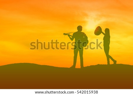 Silhouette a Woman and Man at the sunset. Being sing a song and dance have fun,guitar.