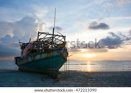 SILHOUETTE ABANDONED FISHER-BOAT ON SAND BANK WITH BEAUTIFUL TWILIGHT SKY BACKGROUND