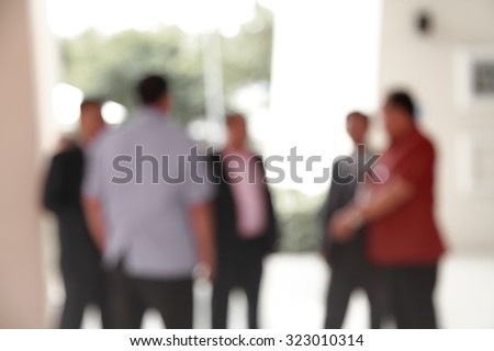 Silhouette action of blur business people men talking about world stock trading under the high roof of building  - stock photo