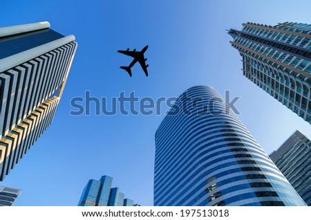 Silhouette aircraft flying over modern building in the business district. - stock photo