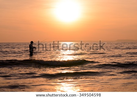 Silhouette angler sunset background. - stock photo